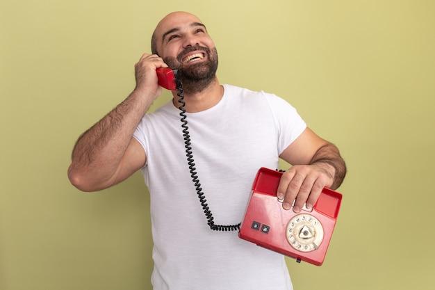 Bebaarde man in wit t-shirt praten over een oude telefoon lachend met blij gezicht staande over groene muur