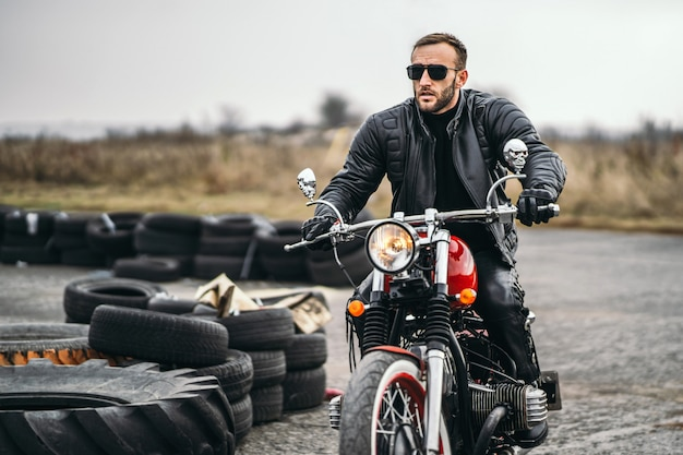 Bebaarde man in zonnebril en lederen jas zittend op een rode motorfiets en kijken op de weg.