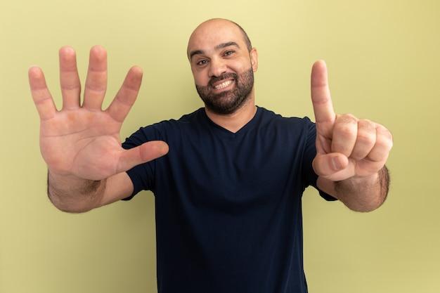Bebaarde man in zwart t-shirt glimlachend tonend nummer zes staande over groene muur