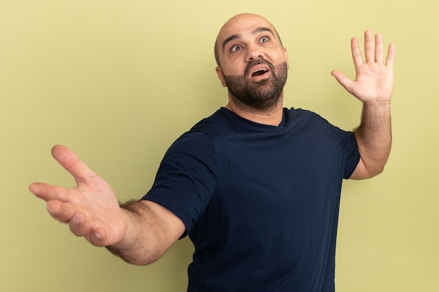 Bebaarde man in zwart t-shirt glimlachend verward wijd openende handen opzoeken die zich over groene muur bevinden
