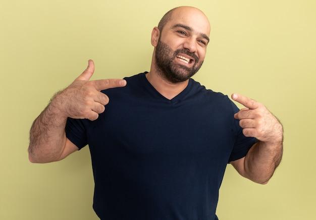 Bebaarde man in zwart t-shirt glimlachend vrolijk wijzend op zichzelf staande over groene muur