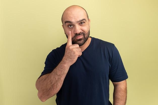 Bebaarde man in zwart t-shirt glimlachend wijzend met wijsvinger naar zijn oog staande over groene muur