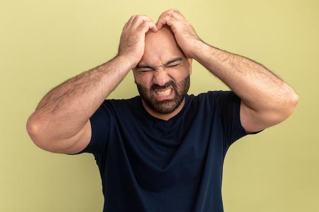 Bebaarde man in zwart t-shirt kijkt geïrriteerd en gefrustreerd met handen op zijn hoofd die wild worden staande over groene muur