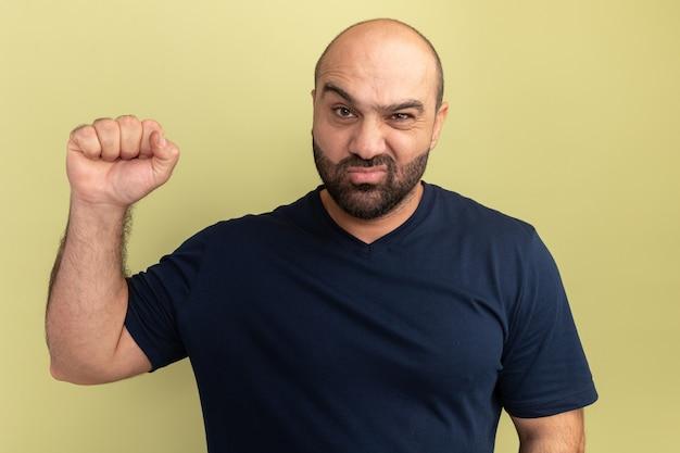 Bebaarde man in zwart t-shirt met fronsend gezicht dat vuist opheft als een winnaar die over groene muur staat
