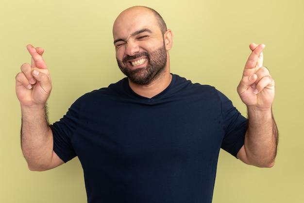 Bebaarde man in zwart t-shirt met gesloten ogen die wenselijke wens maken die vingers kruisen die zich over groene muur bevinden