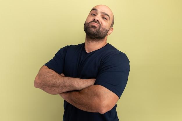 Bebaarde man in zwart t-shirt met zelfverzekerde uitdrukking op slim gezicht met gekruiste armen staande over groene muur