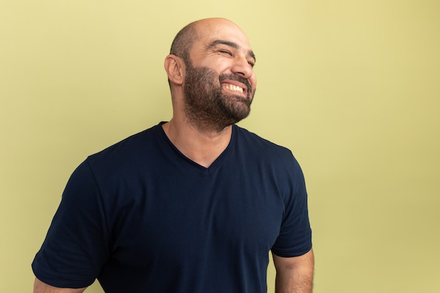 Bebaarde man in zwart t-shirt opzij glimlachend vrolijk blij en positief staande over groene muur