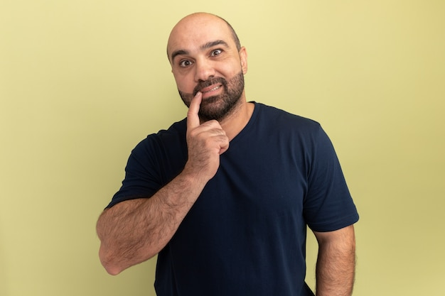 Bebaarde man in zwart t-shirt verward en verrast staande over groene muur