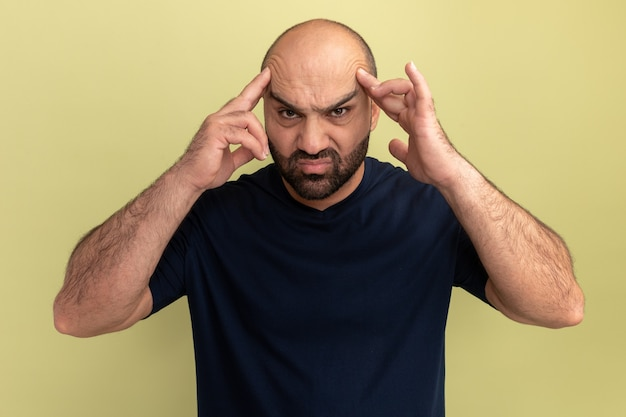 Bebaarde man in zwart t-shirt ziet er onwel en geïrriteerd uit en raakt zijn hoofd aan die lijdt aan sterke hoofdpijn die over groene muur staat