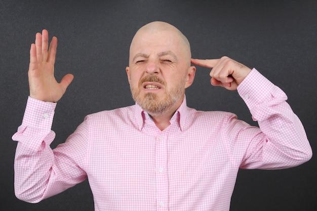 Bebaarde man is erg emotioneel gestrest terwijl hij zijn handen bij zijn hoofd houdt