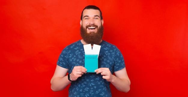 Bebaarde man is erg opgewonden over zijn reis terwijl hij zijn paspoort en tickets vasthoudt.