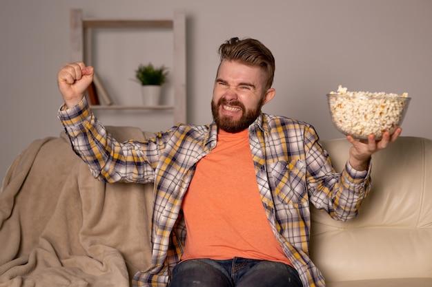 Bebaarde man kijken naar film of sport games tv popcorn eten in huis 's nachts. bioscoop, kampioenschap
