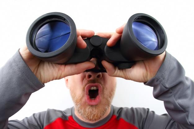 Bebaarde man kijkt door een verrekijker in de verte Premium Foto