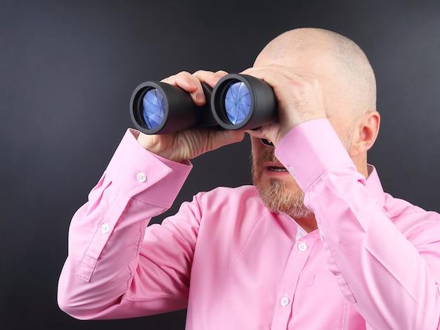 Bebaarde man kijkt door een verrekijker op donkere achtergrond
