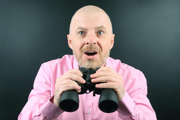 Bebaarde man kijkt door een verrekijker op zwart