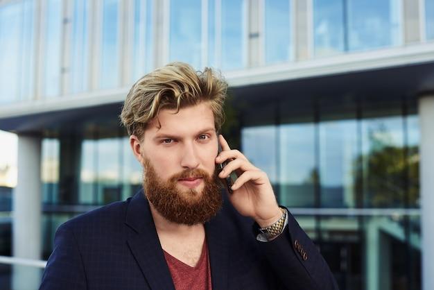 Bebaarde man kijkt in de cameta en praat via de mobiele telefoon