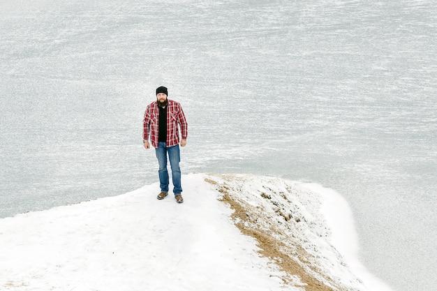 Bebaarde man kijkt naar een bevroren meer in de winter