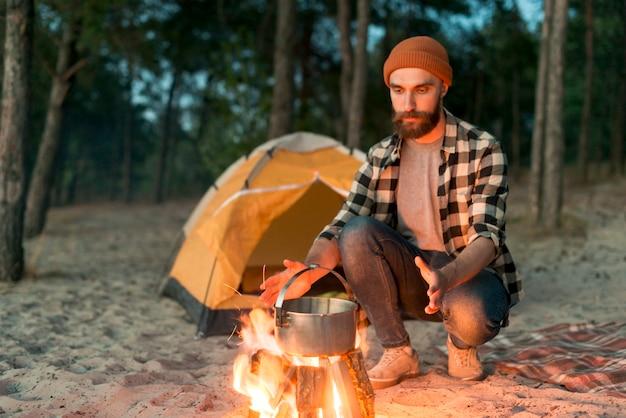 Bebaarde man kijkt naar vuur