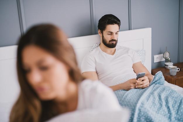 Bebaarde man kijkt naar zijn telefoon terwijl hij in bed ligt met een jonge vrouw met bruin haar.