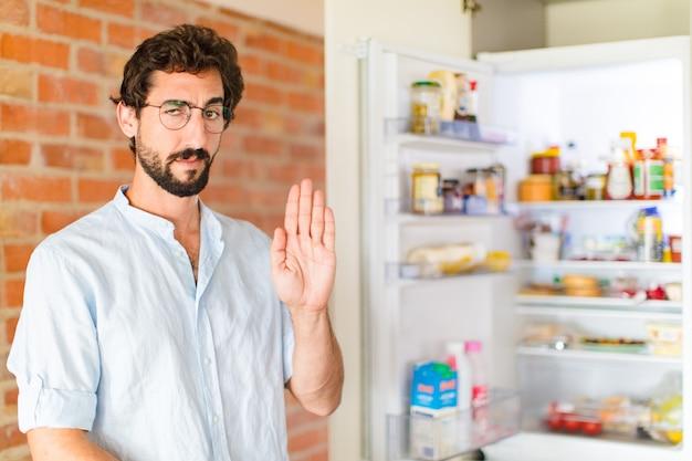 Bebaarde man kijkt serieus, streng, ontevreden en boos met open palm stop gebaar maken
