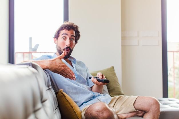 Bebaarde man kijkt verbaasd en geschokt, met open mond een voorwerp met een open hand opzij