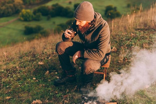 Bebaarde man koffie drinken in de ochtend in de buurt van kampvuur