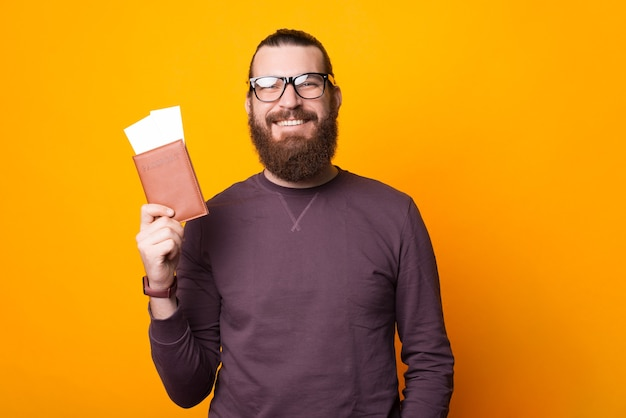 Bebaarde man lacht naar de camera en houdt een paspoort met twee kaartjes erin in de buurt van een gele muur