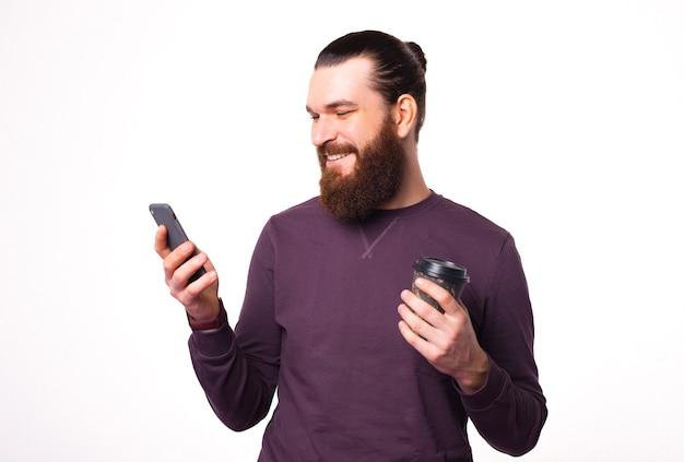 Bebaarde man lacht naar zijn telefoon en houdt een kop warme drank