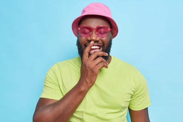 Bebaarde man lacht vrolijk toont witte perfecte tanden houdt ogen gesloten draagt roze panama hartvormige zonnebril casual groen t-shirt drukt positieve emoties uit geïsoleerd op blauwe studio muur