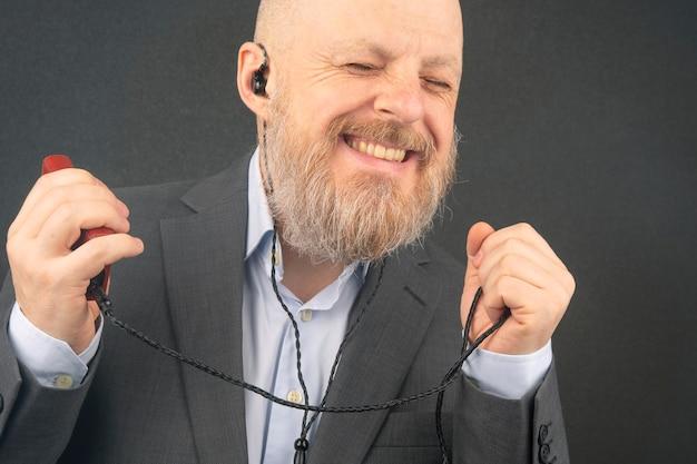 Bebaarde man luistert graag naar zijn favoriete muziek via een audiospeler in een kleine koptelefoon. audiofiel en muziekliefhebber. muziek en hifi-geluid.