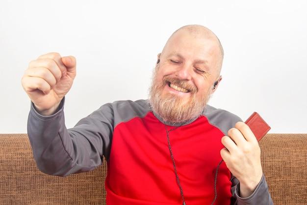 Bebaarde man luistert graag thuis naar zijn favoriete muziek met een audiospeler in een kleine koptelefoon.