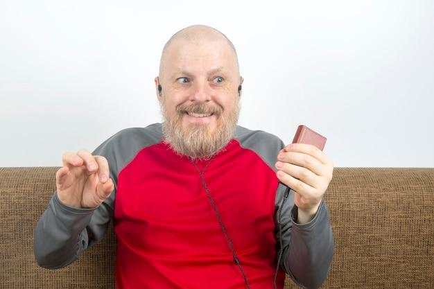 Bebaarde man luistert thuis met plezier naar zijn favoriete muziek van de telefoon met een kleine koptelefoon. audiofiel en muziekliefhebber. muziek en hifi-geluid.