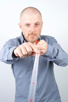 Bebaarde man maakt een meetlint centimeter