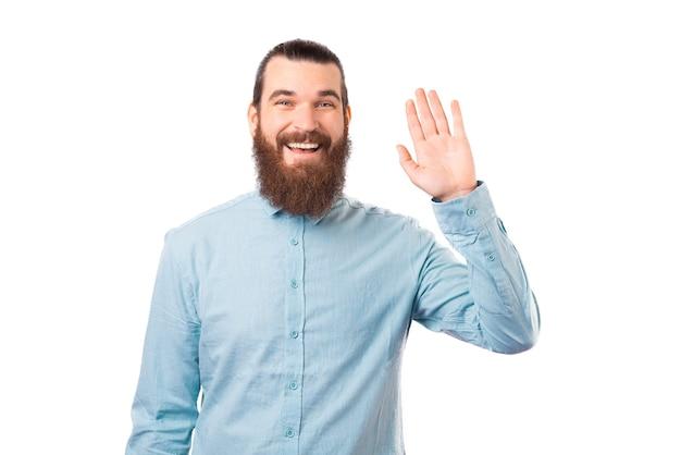 Bebaarde man maakt hallo gebaar om iemand te begroeten.