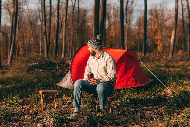 Bebaarde man met afhaalmaaltijden kopje rusten in de buurt van tent