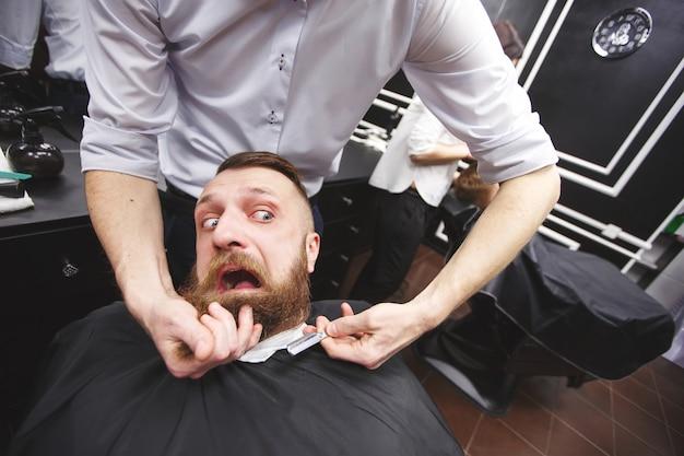 Bebaarde man met angst zit in een kapperszaak.