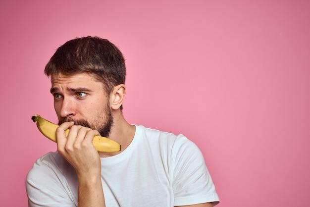 Bebaarde man met banaan in hand op roze achtergrond.