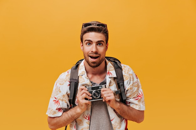 Bebaarde man met blauwe ogen en stijlvol kapsel in wit bedrukte outfit en rugzak poseren met camera op oranje muur