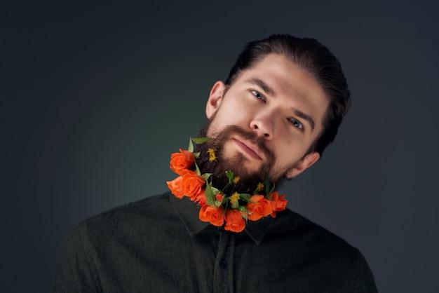 Bebaarde man met bloemen in een baard in een shirt donkere achtergrond