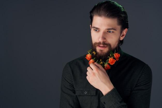 Bebaarde man met bloemen zwart shirt studio poseren