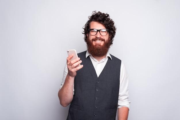 Bebaarde man met bril met een telefoon