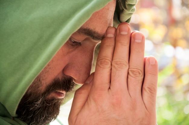 Bebaarde man met capuchon is bidden