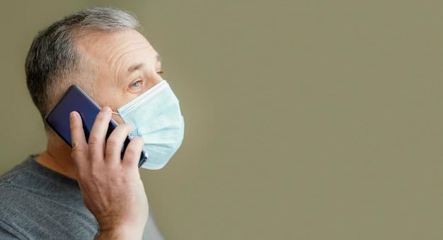 Bebaarde man met chirurgisch masker met behulp van telefoon