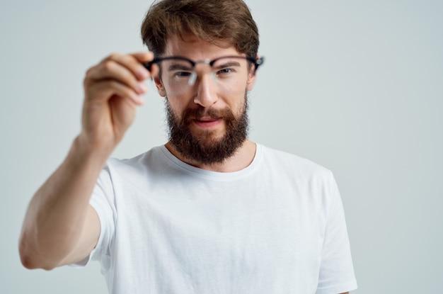Bebaarde man met een bril in de hand zichtproblemen close-up