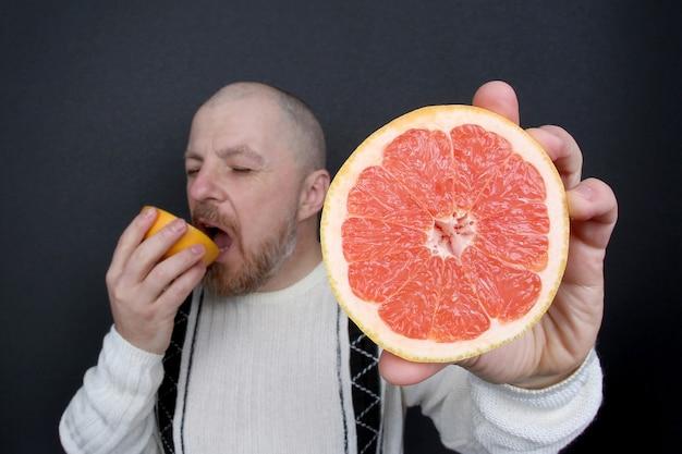 Bebaarde man met een gesneden grapefruit in zijn handen