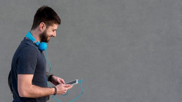 Bebaarde man met een koptelefoon op de nek met behulp van de tablet