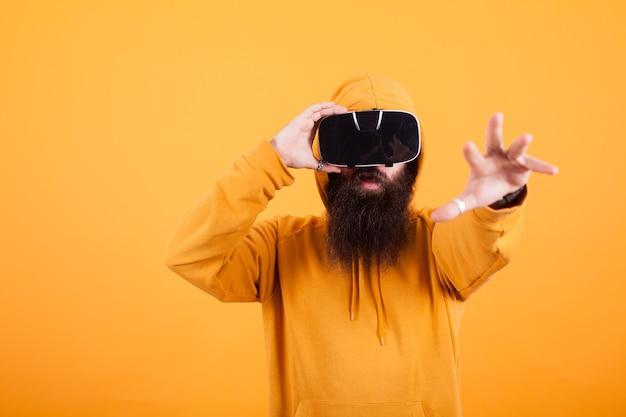 Bebaarde man met een virtual reality-headset die met zijn hand over gele achtergrond reikt. gele hoodie. knappe man. hipster-man.