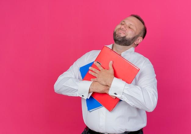 Bebaarde man met een wit overhemd met mappen die dankbaar en giftige emoties voelen met gesloten ogen over roze