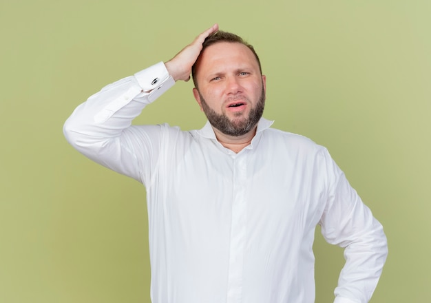 Bebaarde man met een wit overhemd op zoek verward met de hand op zijn hoofd voor een fout die over de lichte muur staat