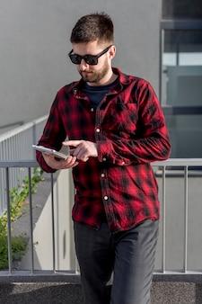 Bebaarde man met een zonnebril met behulp van tablet pc